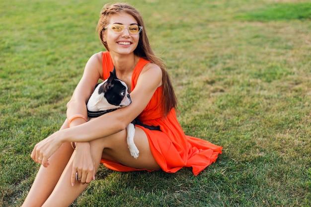 Glückliche hübsche frau, die auf gras im sommerpark sitzt, boston-terrier-hund hält, positive stimmung lächelt, orange kleid trägt, trendigen stil, mit haustier spielend