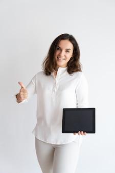 Glückliche hübsche frau, die den tablet-computer, seinen schirm zeigend hält und betrachten kamera