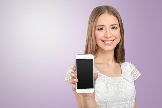 Glückliche hübsche frau, die einen leeren intelligenten telefonschirm zeigt