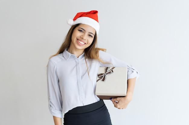 Glückliche hübsche frau, die geschenkbox unter ihrer achselhöhle hält