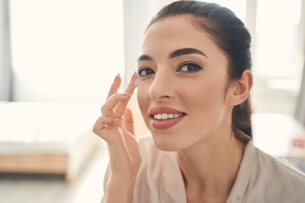 Glückliche hübsche frau, die ihre morgendlichen kosmetischen verfahren genießt und etwas anti-aging-creme auf eine saubere, gesunde haut ihres gesichts auftragen