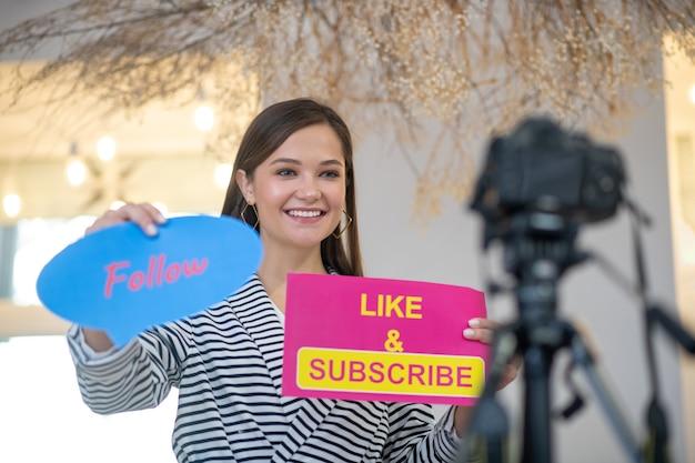Glückliche hübsche frau, die lächelt, während sie neue anhänger zu ihrer seite im sozialen netzwerk anzieht