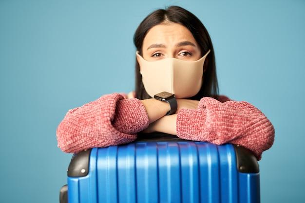 Glückliche hübsche frau, die mit blauem koffer reisen wird