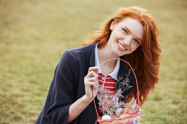 Glückliche hübsche frau, die picknickkorb mit ostereiern im freien hält