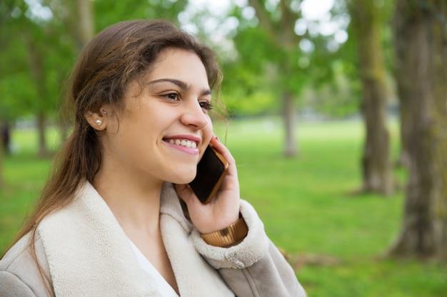 Glückliche hübsche frau, die um smartphone im park ersucht