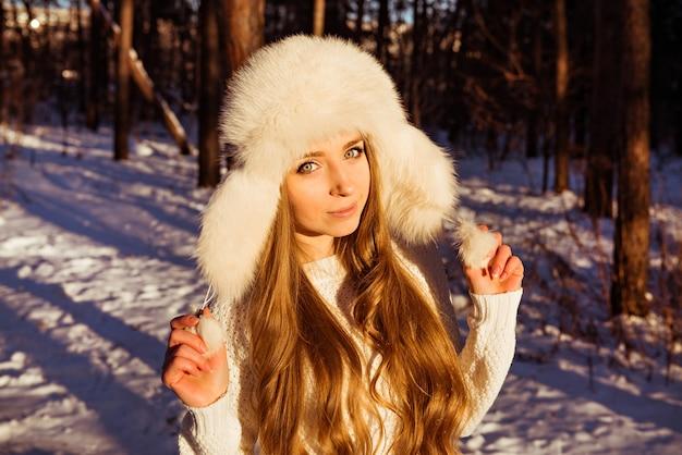 Glückliche hübsche frau, die weiße pelzmütze im winterwald hält