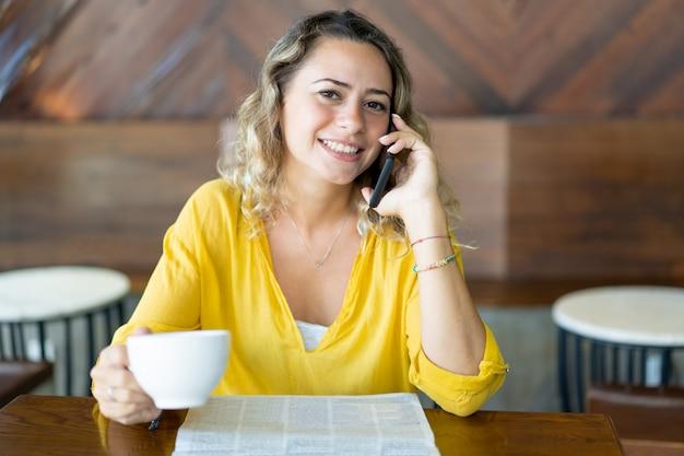 Glückliche hübsche frau im café, das am telefon spricht