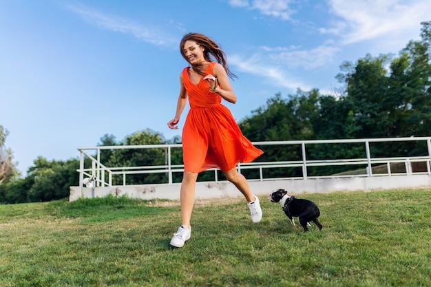 Glückliche hübsche frau im park, der mit boston-terrier-hund läuft, positive stimmung lächelt, trendiger sommerstil, orange kleid trägt, mit haustier spielt, spaß hat, bunte, aktive wochenendferien, turnschuhe