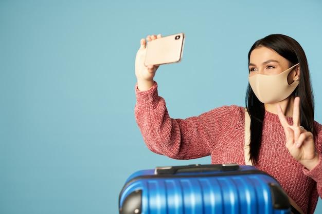 Glückliche hübsche frau in maske mit koffer beim fotografieren auf ihrem smartphone. platz kopieren. konzept der reise, coronavirus