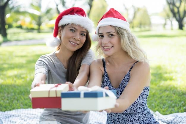 Glückliche hübsche frauen, die sankt-hüte tragen und geschenkboxen geben