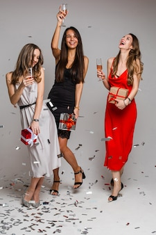 Glückliche hübsche freundinnen, die party mit konfetti genießen, während champagnergläser halten