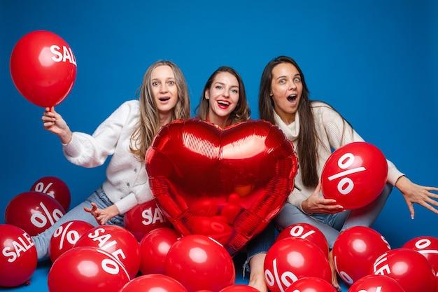 Glückliche hübsche freundinnen sitzen mit roten luftballons des verkaufs, lokalisiert auf blauer wand