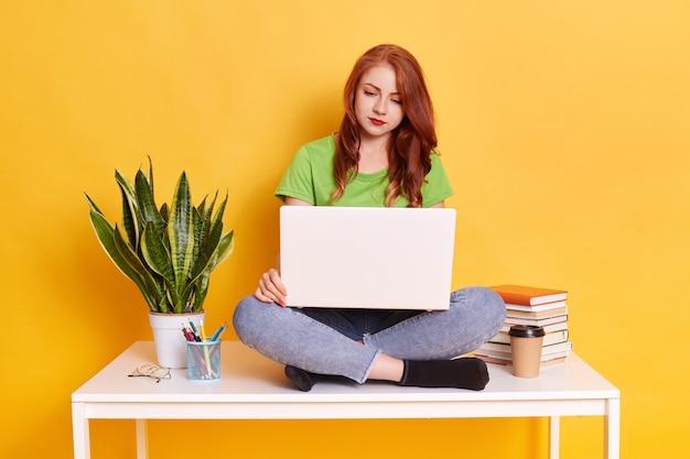 Glückliche hübsche ingwerfrau, die auf tisch sitzt und mit laptop arbeitet