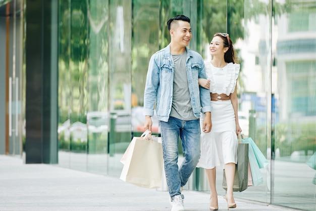 Glückliche hübsche junge asiatische frau, die auf ihren freund schaut, wenn sie nach dem einkaufen draußen gehen