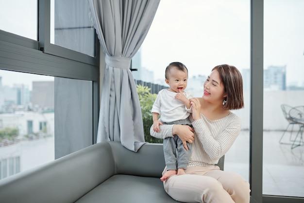Glückliche hübsche junge asiatische frau, die kleine tochter betrachtet, die auf ihren schoß steht
