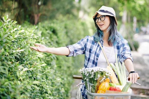Glückliche hübsche junge asiatische frau in den gläsern und im eimerhut, die fahrrad fahren und blätter von straßenrandbüschen berühren