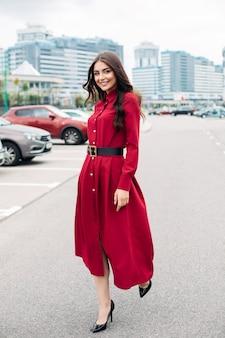 Glückliche hübsche junge dame im roten kleid, die kamera beim gehen entlang der straße in der modernen stadt betrachtet. lifestyle-konzept