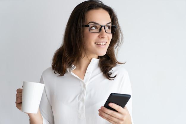 Glückliche hübsche junge frau, die becher und smartphone hält
