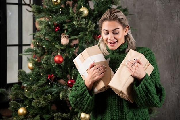 Glückliche hübsche junge frau, die geschenkbox nahe einem weihnachtsbaum hält