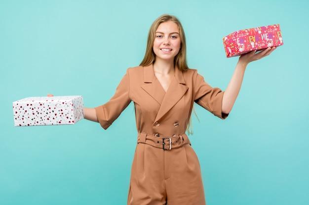 Glückliche hübsche junge frau, die geschenkbox über blauem hintergrund hält.