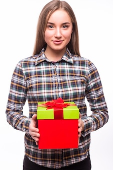Glückliche hübsche junge frau, die geschenkbox über weißer wand hält