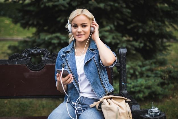 Glückliche hübsche junge frau, die musik in den kopfhörern und im smartphone beim sitzen auf der bank in der stadt hört