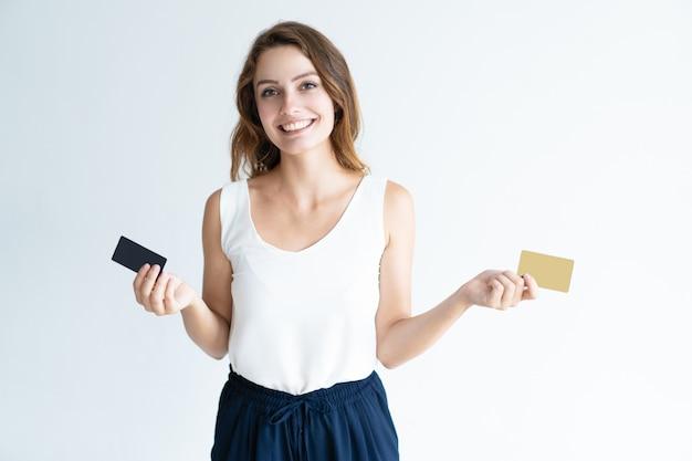 Glückliche hübsche junge frau, die zwei plastikkarten hält