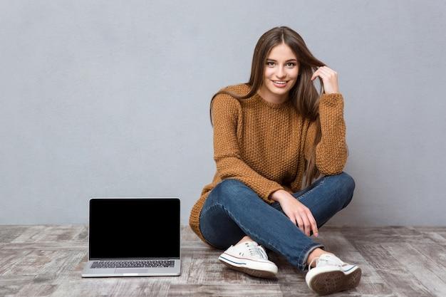 Glückliche hübsche junge frau in braunem pullover, jeans und turnschuhen, die auf holzboden in der nähe des laptops sitzt