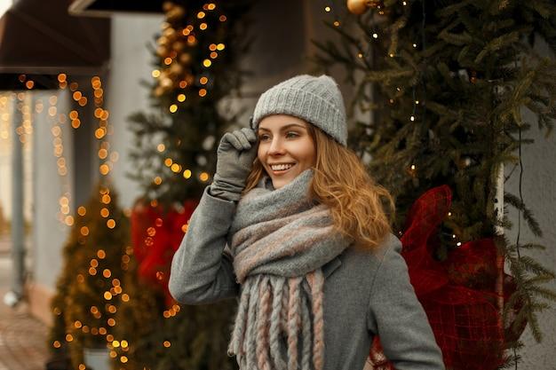 Glückliche hübsche junge frau mit einem magischen lächeln in einem modischen grauen mantel mit einer stilvollen strickmütze und einem modischen schal nahe den lichtern in der stadt an den winterferien