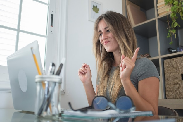 Glückliche hübsche junge weibliche leute genießen online-videokonferenz mit laptop und internetverbindung