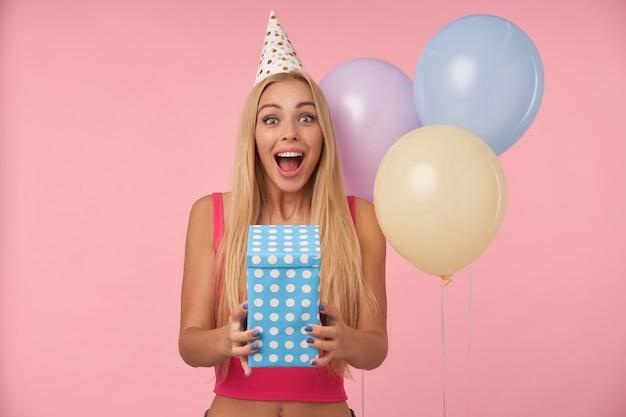 Glückliche hübsche langhaarige frau mit blondem haar, das überrascht kamera betrachtet und augen und mund weit geöffnet hält, geburtstag mit mehrfarbigen luftballons feiern, lokalisiert über rosa hintergrund