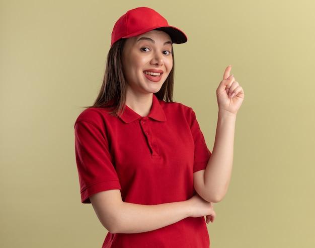 Glückliche hübsche lieferfrau in uniform zeigt nach oben