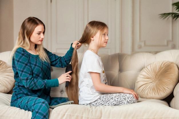 Glückliche hübsche mutter und ihre kleine tochter in freizeitkleidung, die ihr haar auf dem sofa im wohnzimmer sanft kämmt. konzept, zeit zusammen mit kindern und familie zu verbringen, schöne beziehungen. platz kopieren