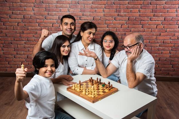 Glückliche indische asiatische mehrgenerationenfamilie mit sechs spielern, die schach oder shatranj spielt, ein beliebtes brettspiel, das weiße tücher gegen rote backsteinmauer trägt