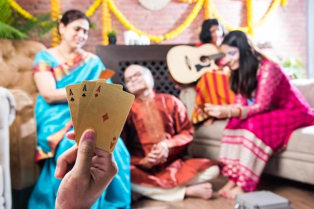 Glückliche indische familie, die in der diwali-festivalnacht in traditioneller kleidung zu hause teen patti oder drei kartenspiel spielt