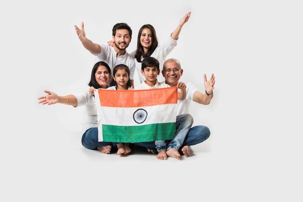 Glückliche indische familie mit nationaler trikolore beim sitzen isoliert auf weißem hintergrund, selektiver fokus