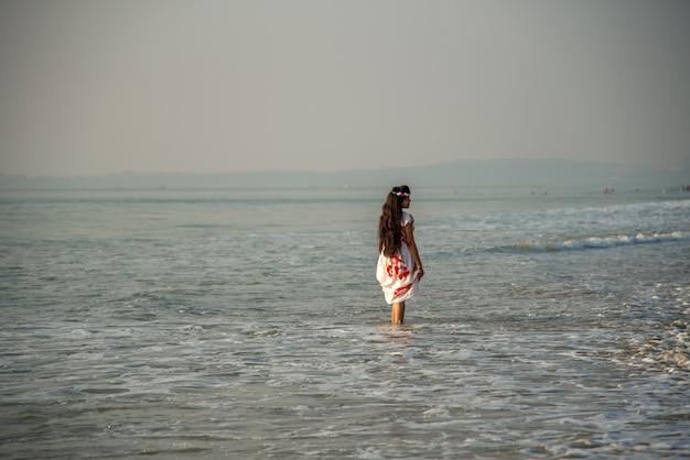 Glückliche indische frau, die einen urlaub am strand genießt.