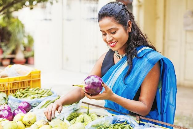 Glückliche indische frau im saree, die auberginen auf dem markt auswählt
