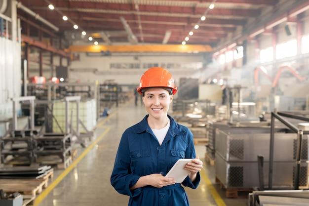 Glückliche ingenieurin in helm und overall, die sie während der arbeit in einer großen industrieanlage betrachtet