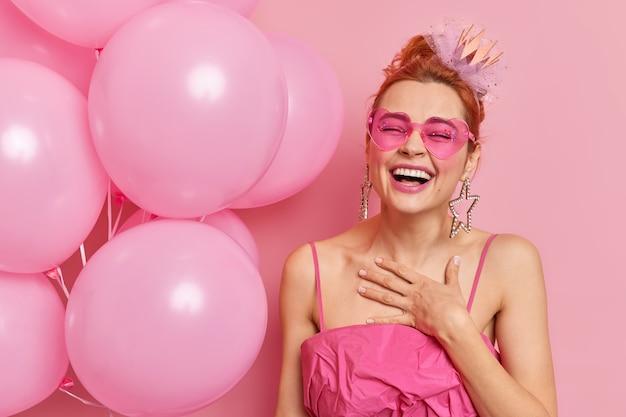 Glückliche ingwerfrau fühlt sich zufriedenes lächeln breit hält hand auf brust hat festliche stimmung hält aufgeblasene luftballons kommt auf abschlussfeier