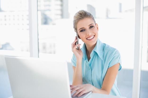 Glückliche intelligente geschäftsfrau am telefon bei der anwendung des laptops
