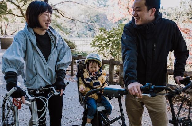 Glückliche japanische familie, die zeit im freien verbringt