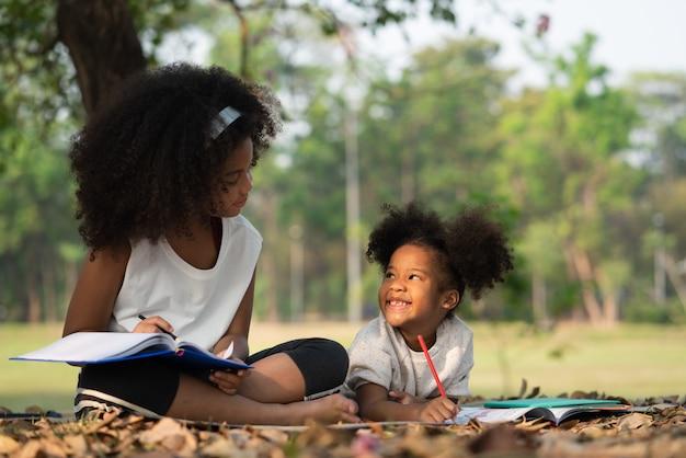 Glückliche jüngere schwester, die lächelt und ihre ältere schwester beim lügenzeichnen im malbuch für kinder im park liegend betrachtet. familien- und beziehungskonzept.