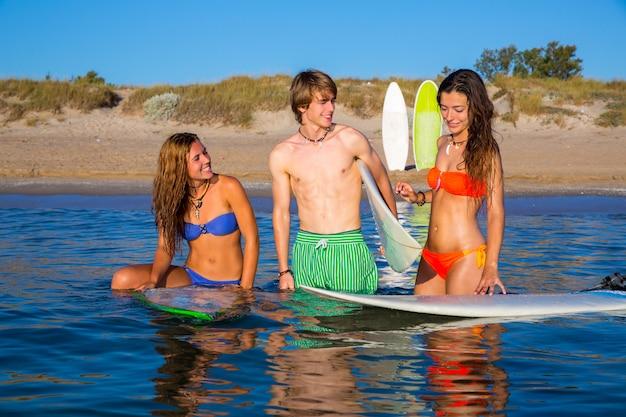 Glückliche jugendlich surfer, die auf strandufer sprechen