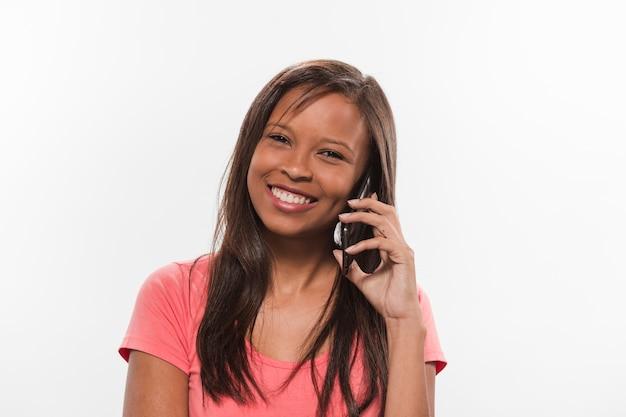Glückliche jugendliche, die auf smartphone spricht