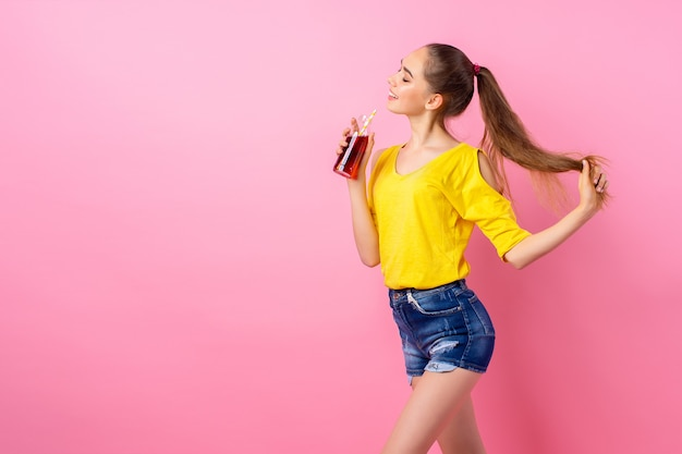 Glückliche jugendliche, die mit flasche des getränks steht