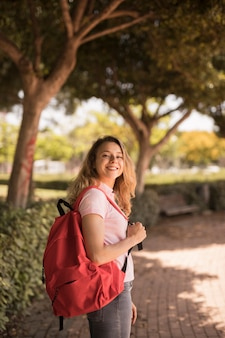 Glückliche jugendliche, die mit rucksack im park lächelt