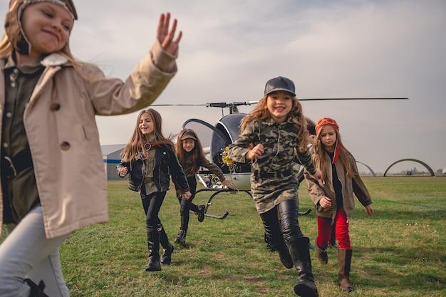 Glückliche jugendliche mädchen, die auf dem flugfeld des aeroclubs laufen