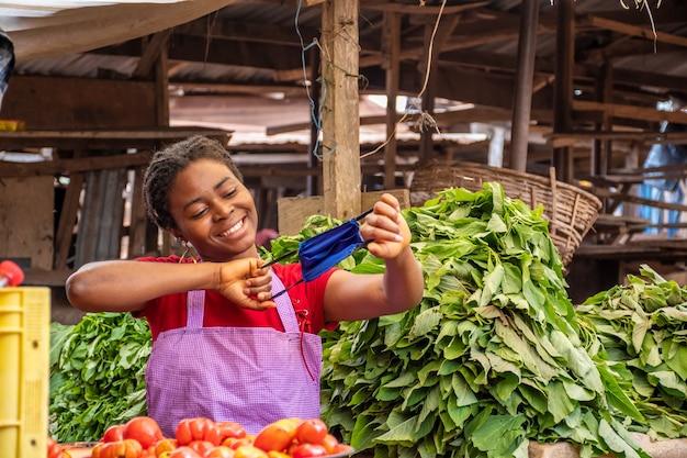 Glückliche junge afrikanerin auf einem lokalen afrikanischen markt, die spielerisch eine gesichtsmaske hält