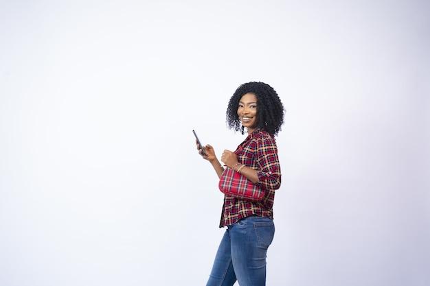 Glückliche junge afrikanerin, die seitlich steht und ihr telefon benutzt